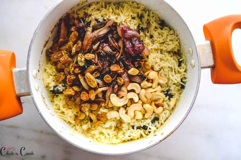 fried garnishes are added to cooked Kashmiri Pulao in deep pot