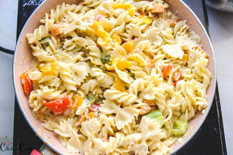 pasta tossed in white sauce in wide sauce pan