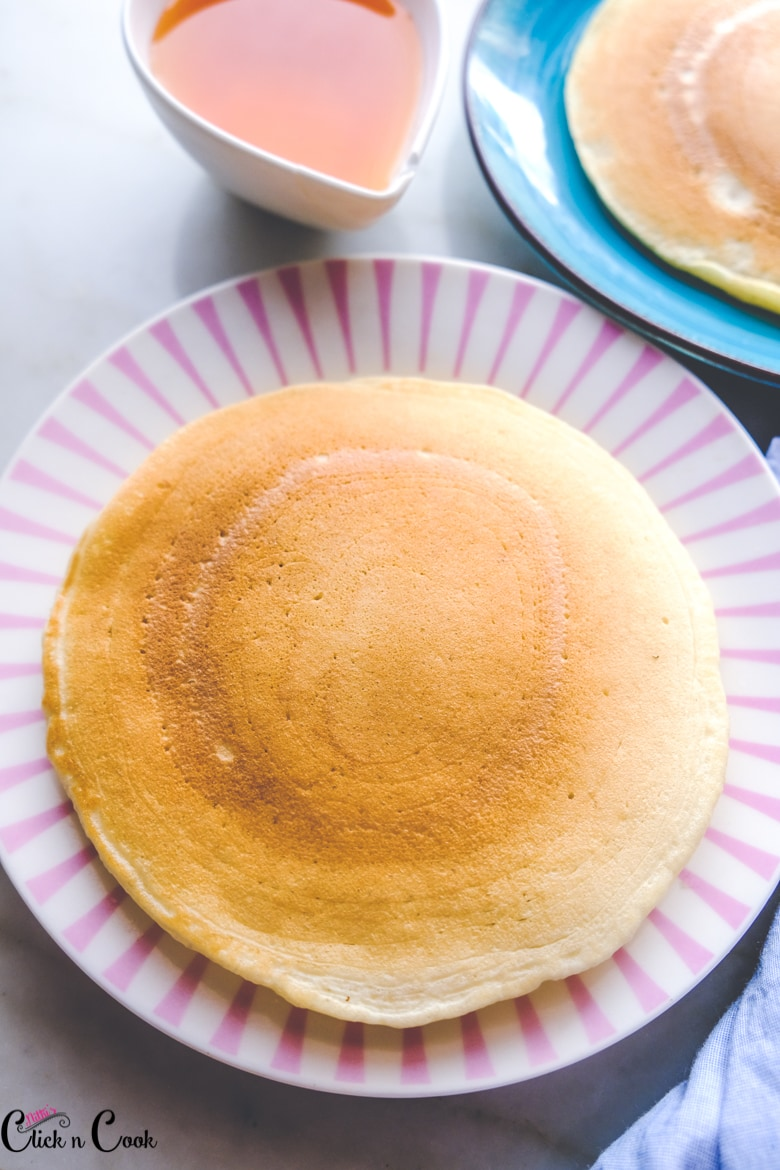pancake recipe with buttermilk is served in pink plate with maple syrup aside