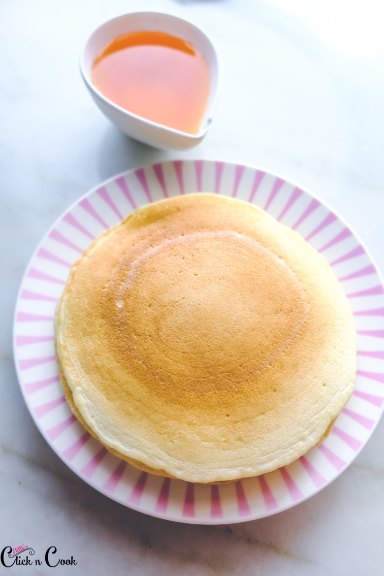 Buttermilk pancakes are served in pink bowl with maple syrup in sauce bowl