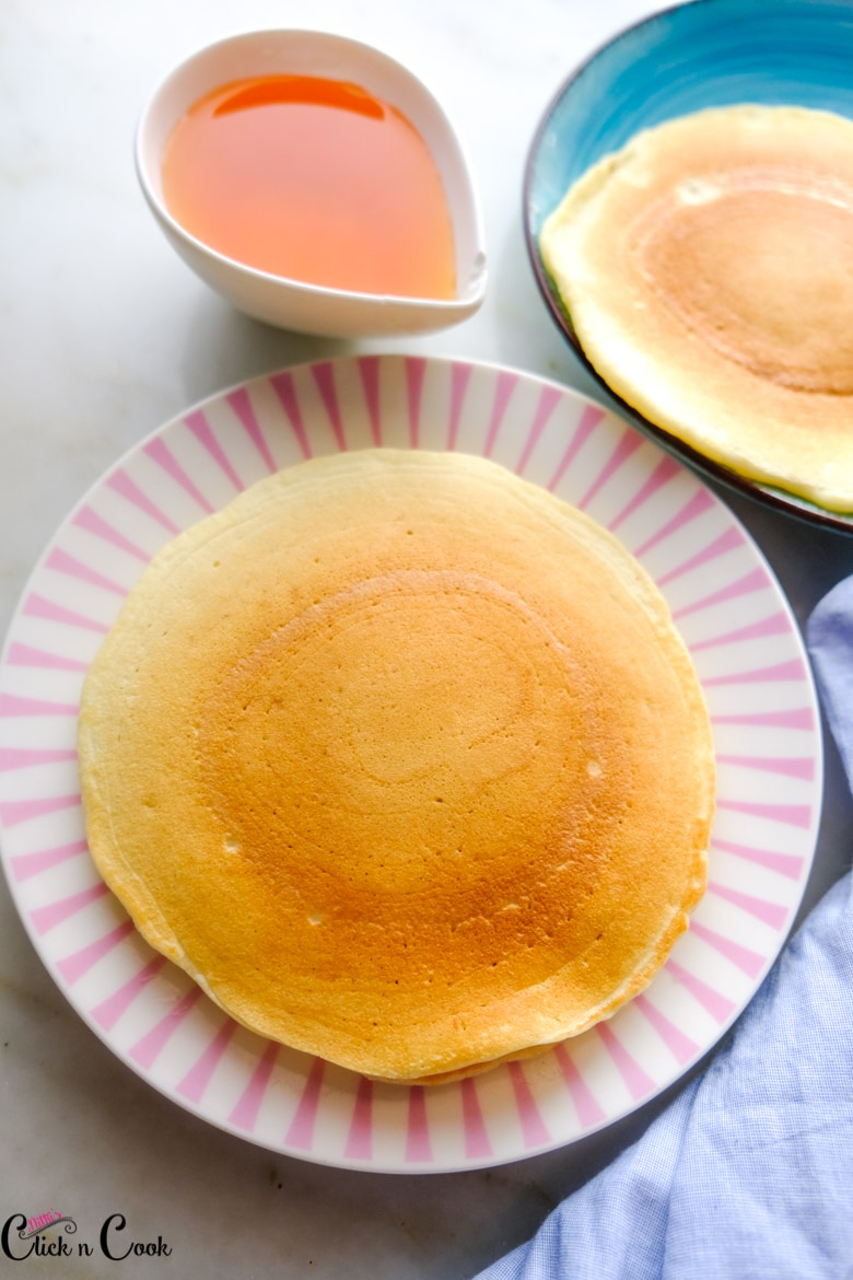 best buttermilk pancake is served in pink plate with maple syrup in sauce bowl