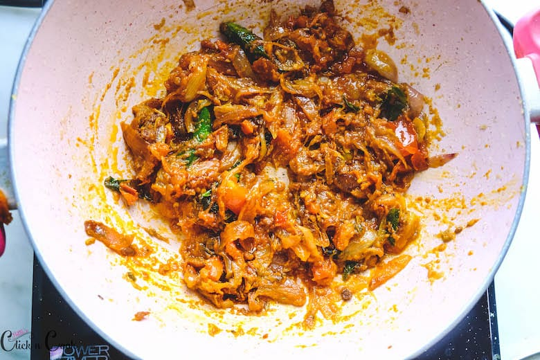 onions and tomato masala is cooked in saute pan