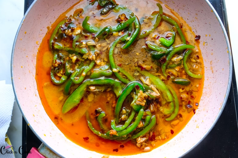 capsicum is cooked with sauce in wide saute pan