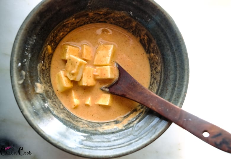 cubed paneer in batter in bowl with wooden spoon