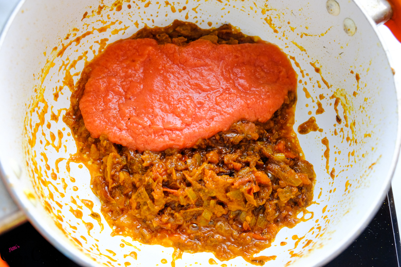 tomato puree is being added to masala in saute pan