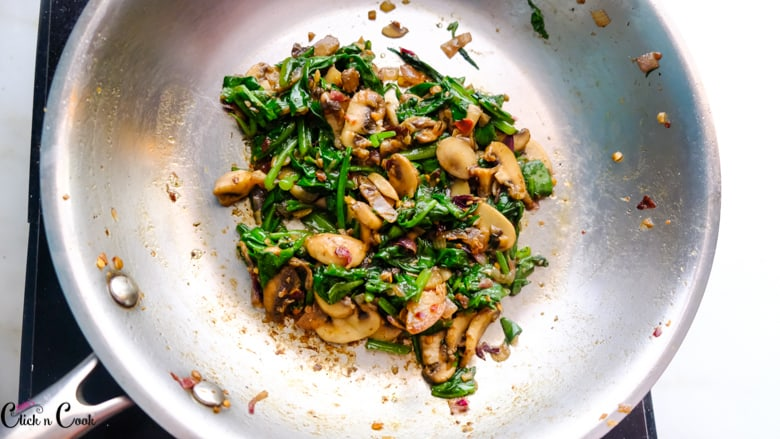 spinach and mushroom is being cooked in saute pan