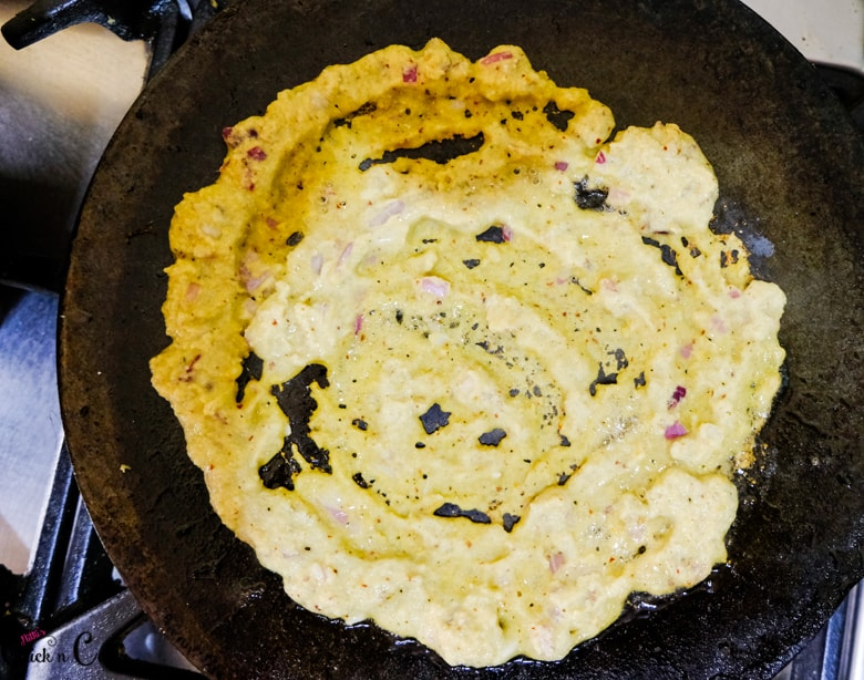 Adai crepe is being cooked in iron pan