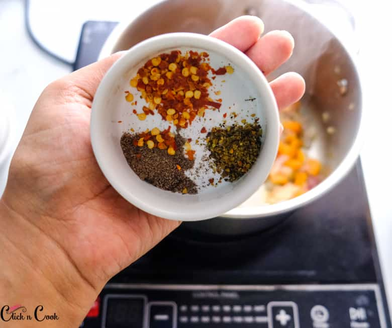 a bowl of chilli flakes, pepper powder and mixed herbs