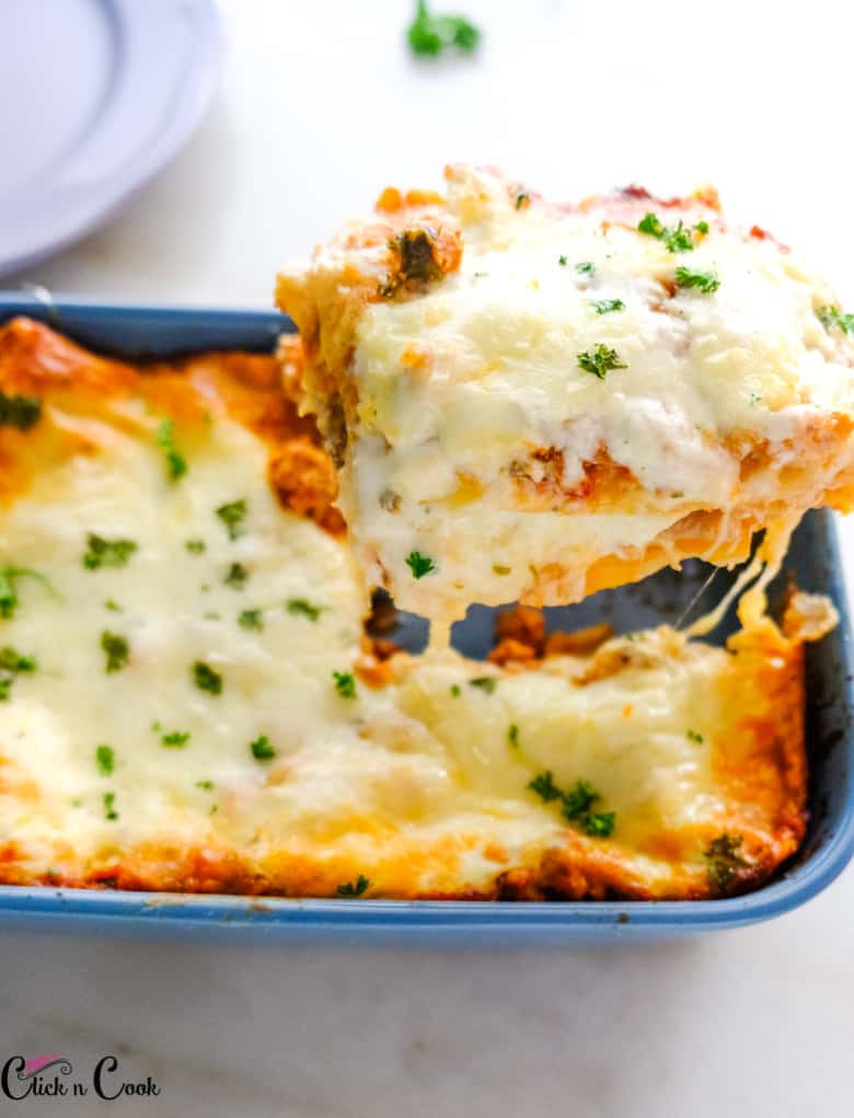 a slice of chicken lasagna is taken from the baking tray