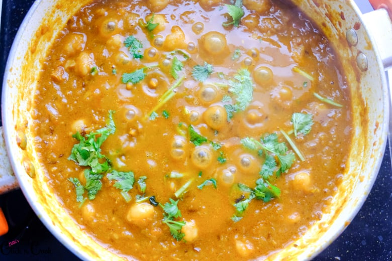 chopped coriander leaves is being sprinkled over the channa masala.