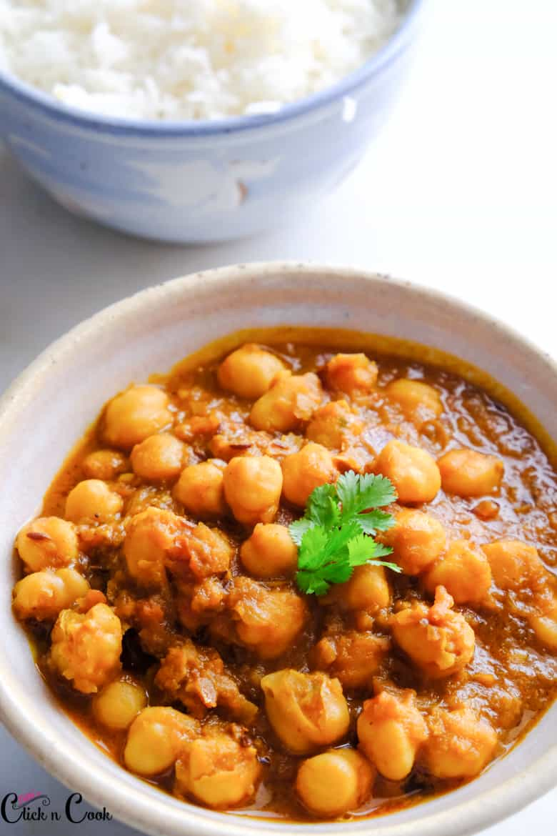 channa masala is served in small bowl with cup of rice aside.