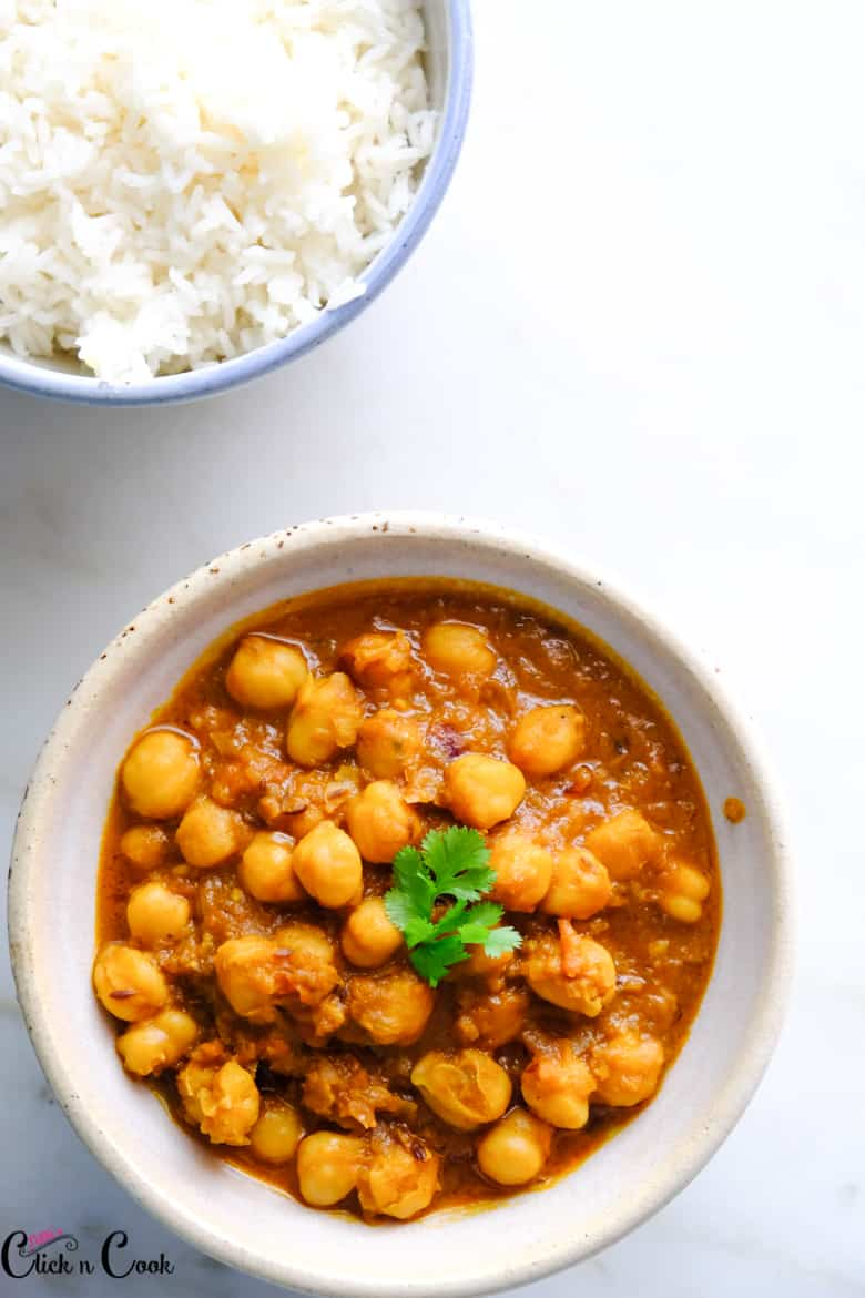 chana masala served in a bowl with cup of rice aside.