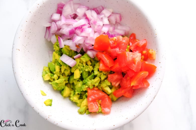 chopped tomato,onion and avacado are in bowl