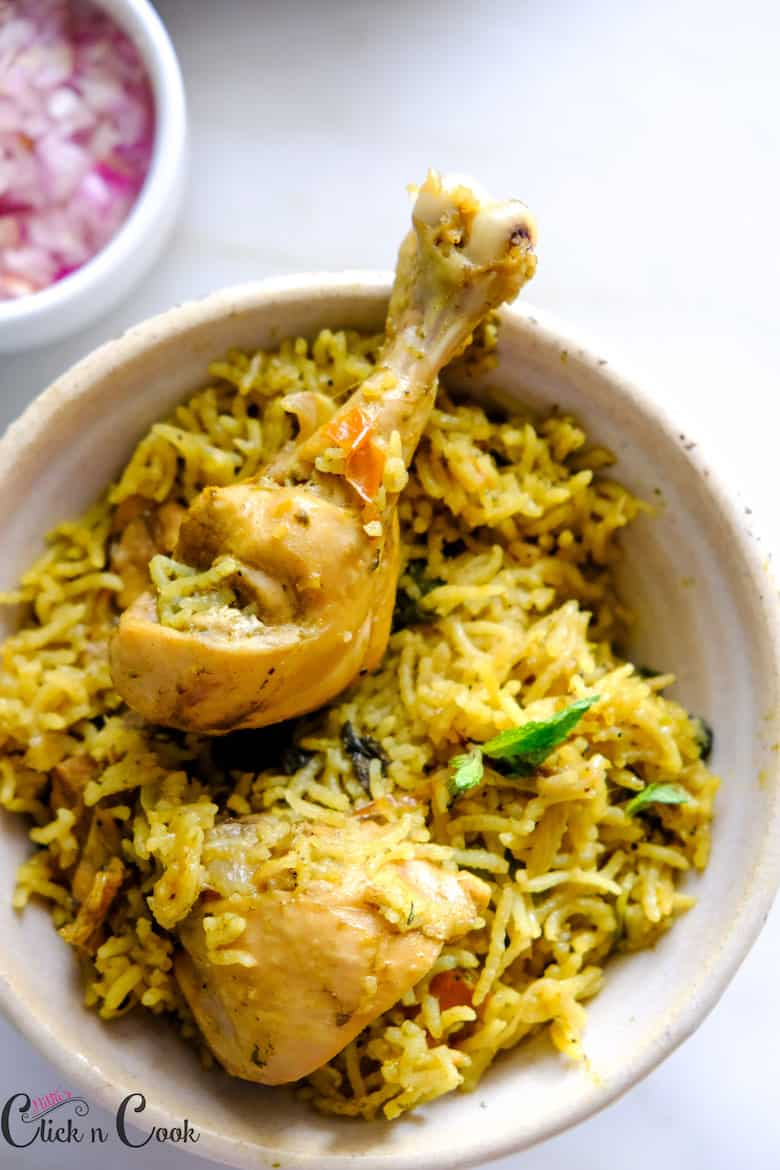 chicken biryani served in bowl with chopped onion in bowl