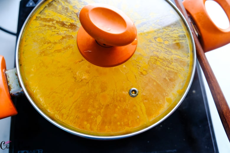 pot is covered with orange lid kept over the stove