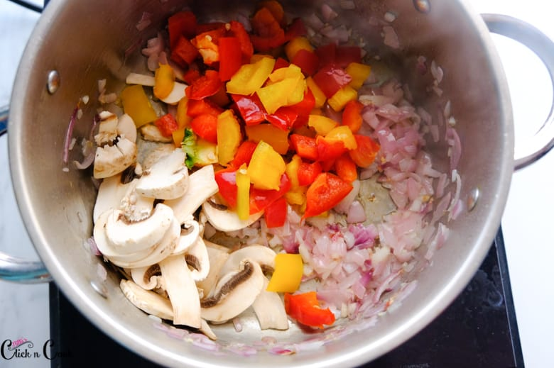 red, yellow capsicum and mushroom, onion are being sauted in deep pot