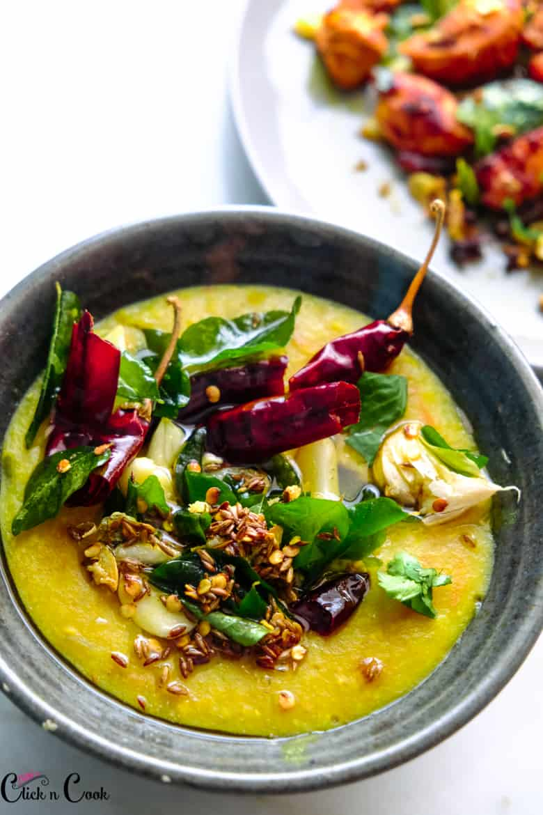 dal tadka served in black bowl topped with red chillies, cumin and garlic
