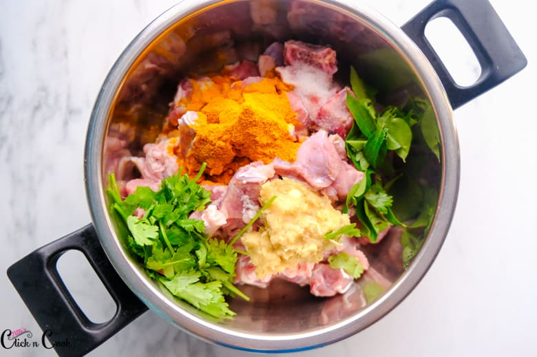 mutton pieces, gingergarlic paste, curry leaves, coriander leaves, turmeric powder are in pressure cooker