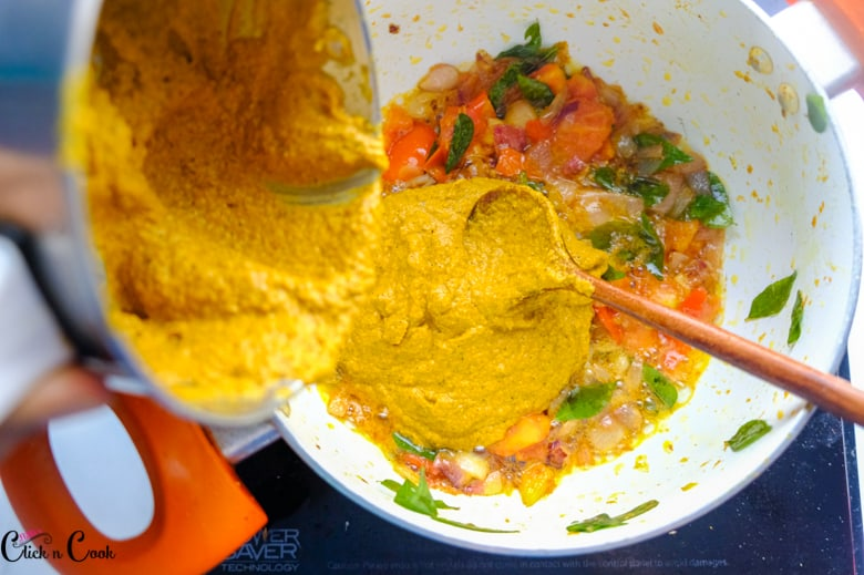 ground masala is being added from the blender to the sauce pan