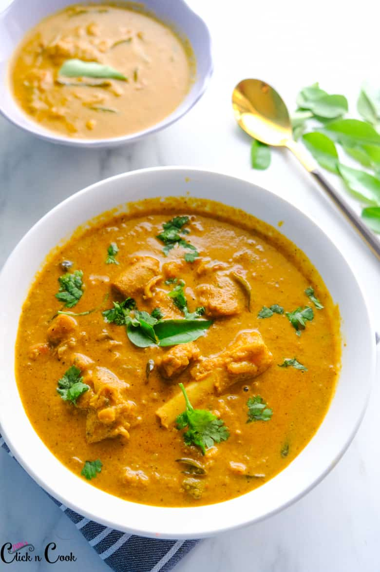 mutton curry is served in white bowl and garnished with chopped coriander leaves with spoon aside