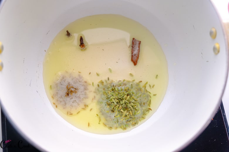 cinnamon, cloves, fennel seeds are being fried in oil in sauce pan