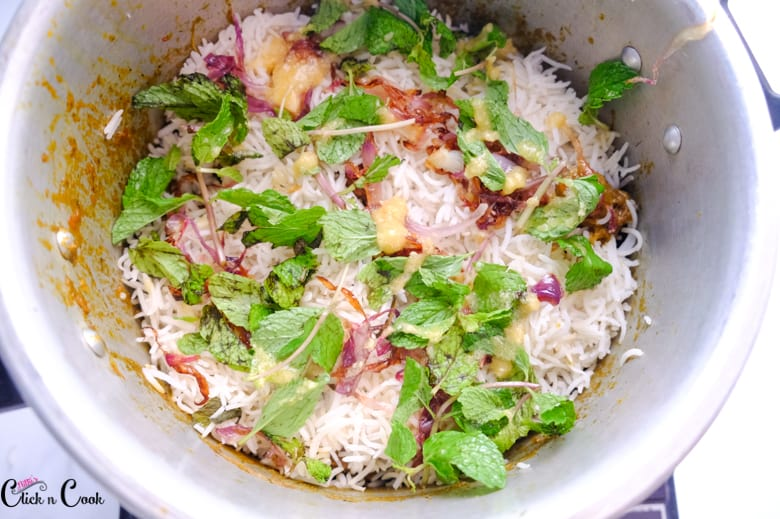 over the cooked rice , mint leaves is added in deep pot.