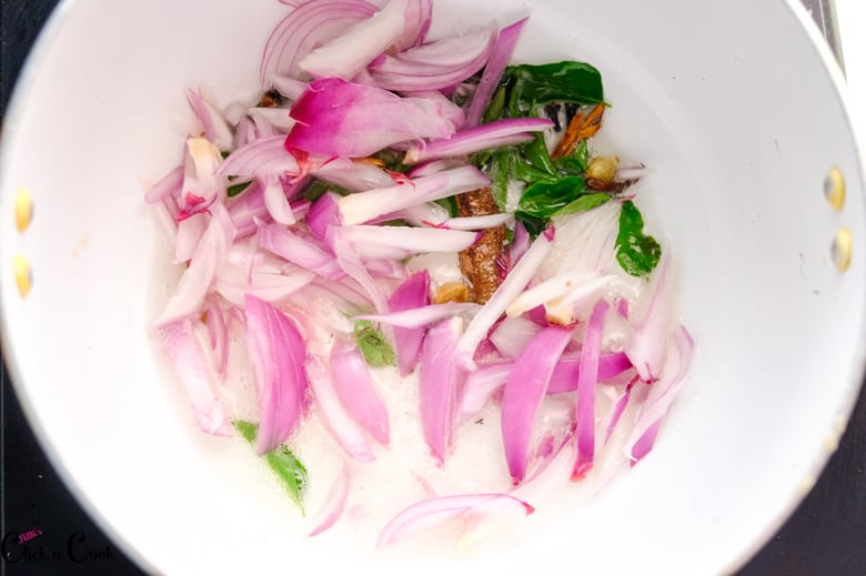 sliced onions, curry leaves are in saute pan