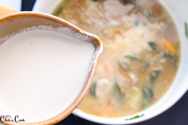 coconut milk is being added to mutton in sauce pan