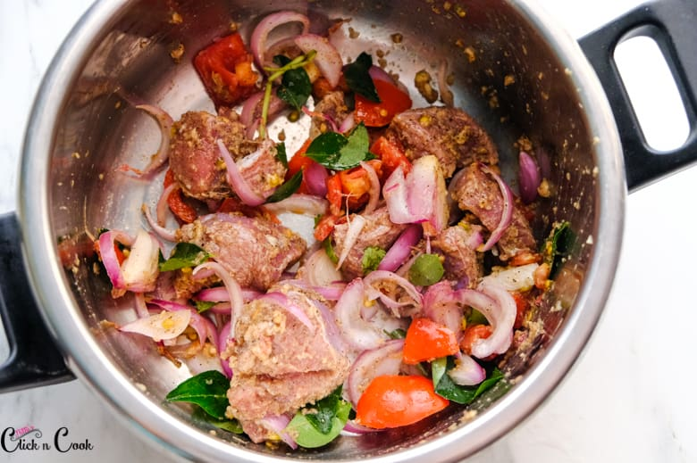 onion, tomato, mutton,curry leaves are in sauce pan