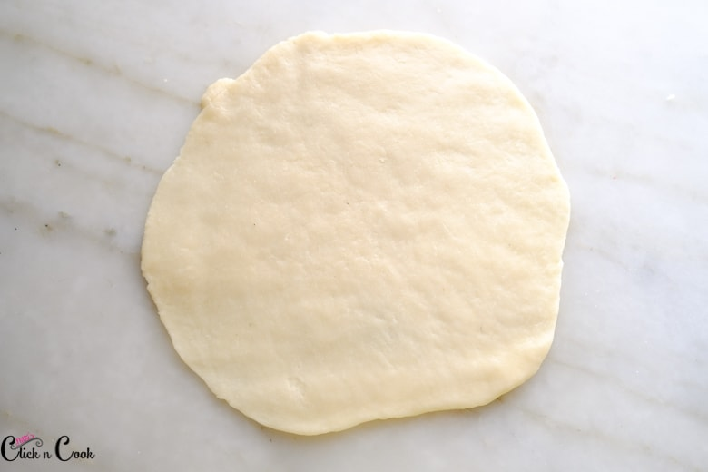 flatted dough disc on a marble white surface