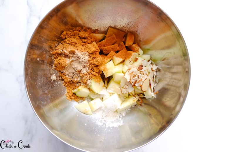 diced apple, cinnamon powder, almond flakes are in steel mixing bowl