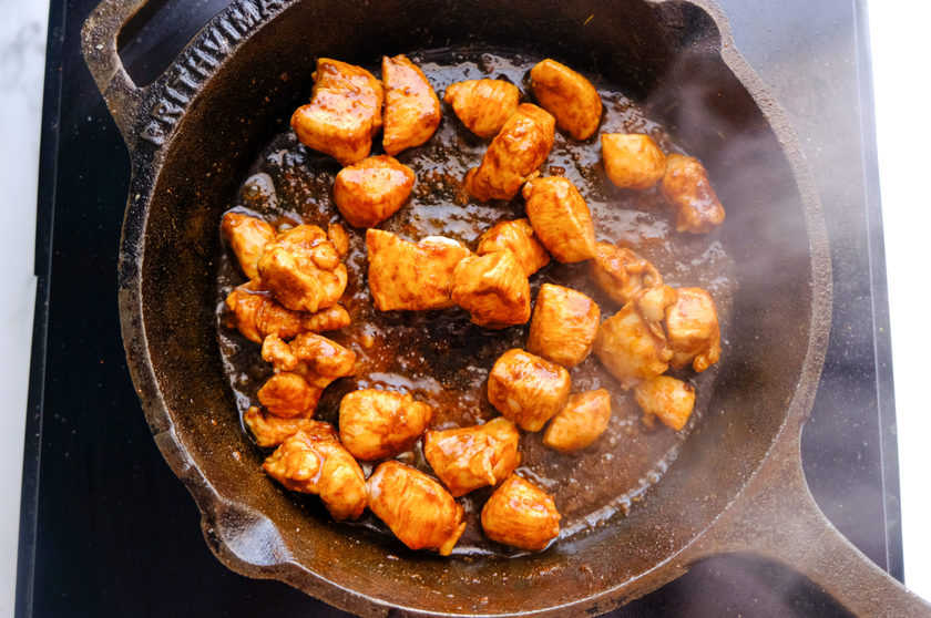 chicken is being fried in cast iron cast pan.