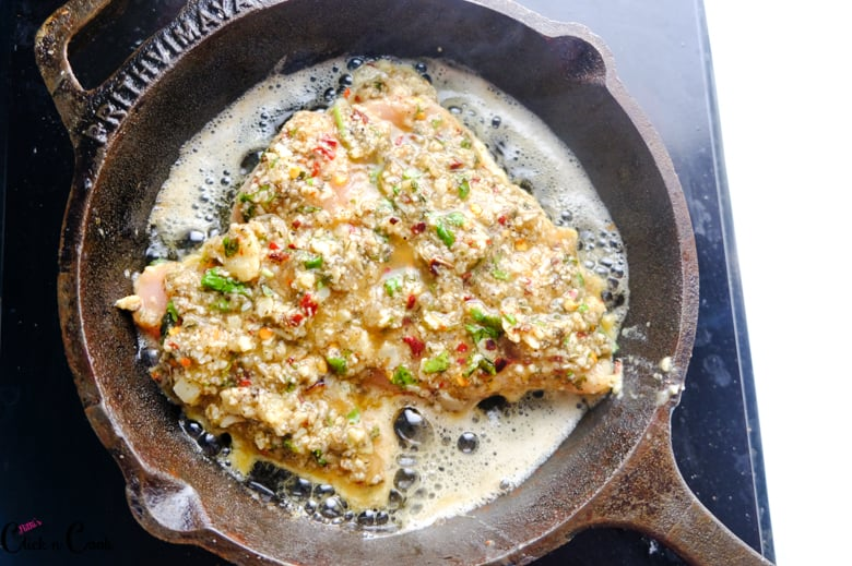 chicken breast is being fried in cast iron pan