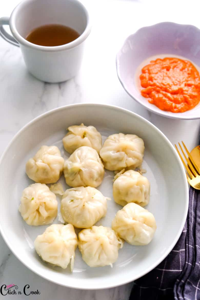 chicken momos served in grey bowl with red sauce and mug of drink aside