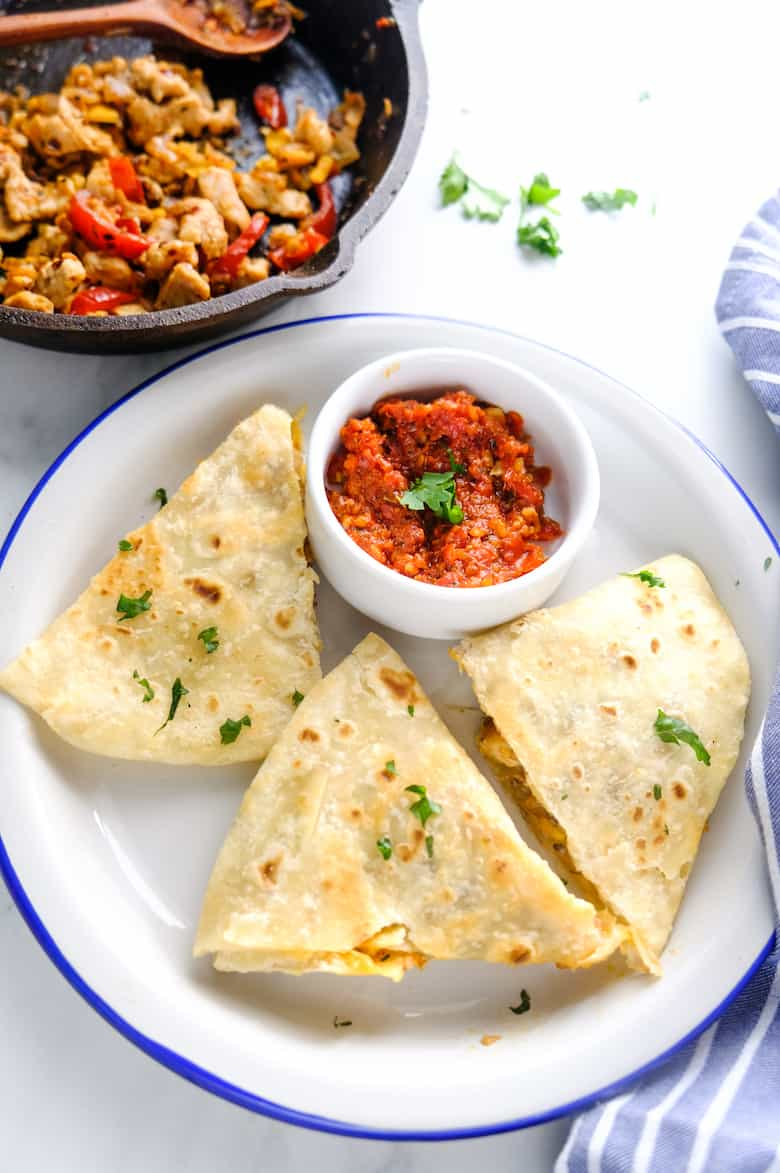 chicken quesadilla served in white plate with small white bowl of tomato dip and chicken filling in cast iron pan kept aside.