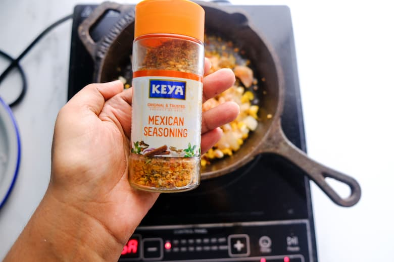 a bottle of mexican seasonings is being added to cast iron pan