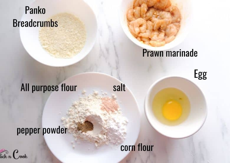 breadcrumbs, flour, egg and shrimps are in white bowls and plate