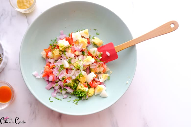 diced eggs, tomato, onion are being mixed in green bowl using wooden spatula