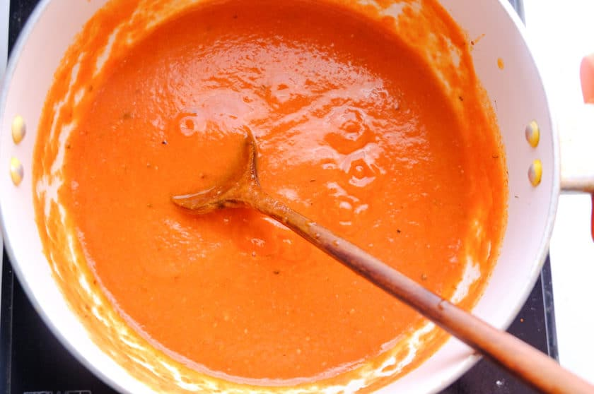 homemade enchilada sauce is being cooked in sauce pan with wooden ladle inside