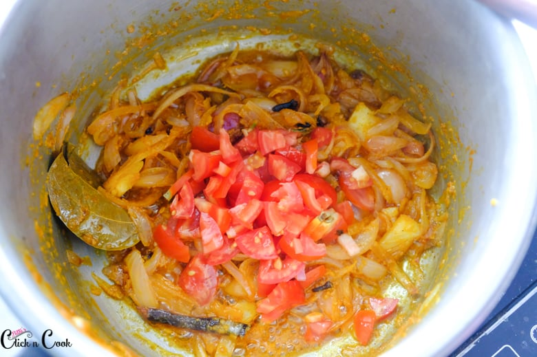 chopped tomato, onions are being cooked in pot