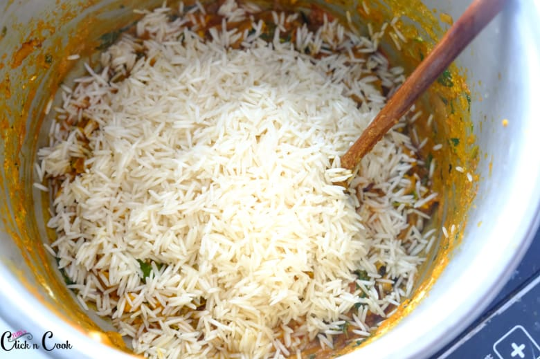 rice is in the pot with wooden spoon