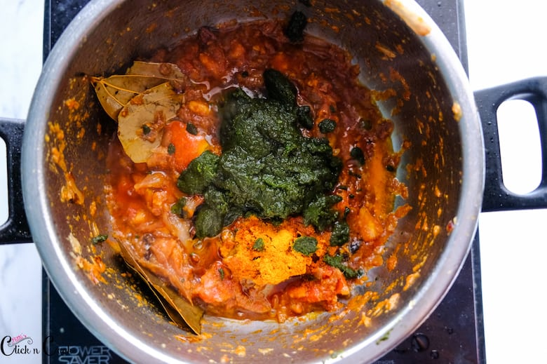 ground mint paste is being cooked in onion tomato masala in sauce pan