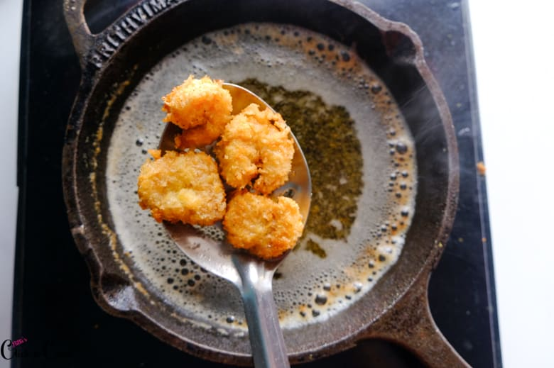 fried shrimps are taken in slotted spoon from the cast iron pan