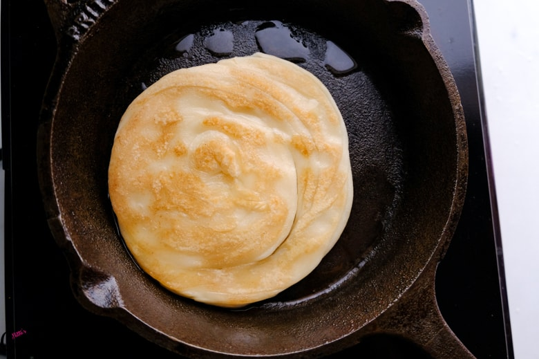 lachha paratha is being cooked in skillet