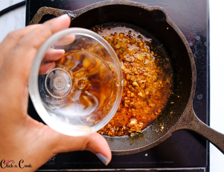 a water from the glass bowl is being added to skillet