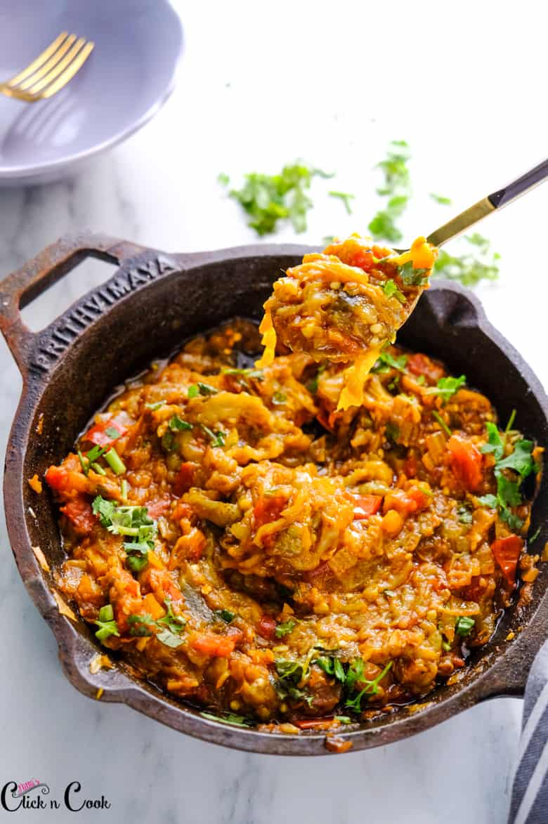 a spoon of baingan bharta is taken from the cast iron pan