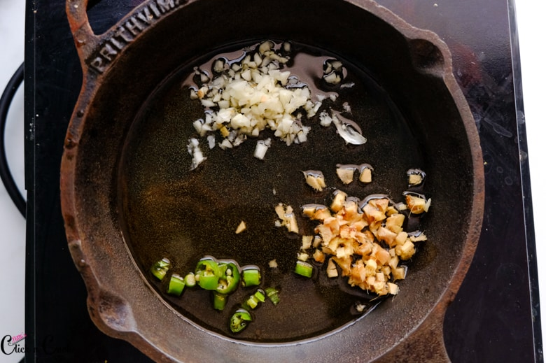 minced ginger garlic and green chilli is cooked in cast iron pan