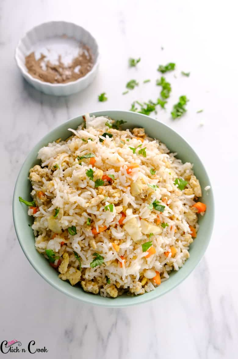 egg fried rice served in green bowl with bowl of pepper powder aside