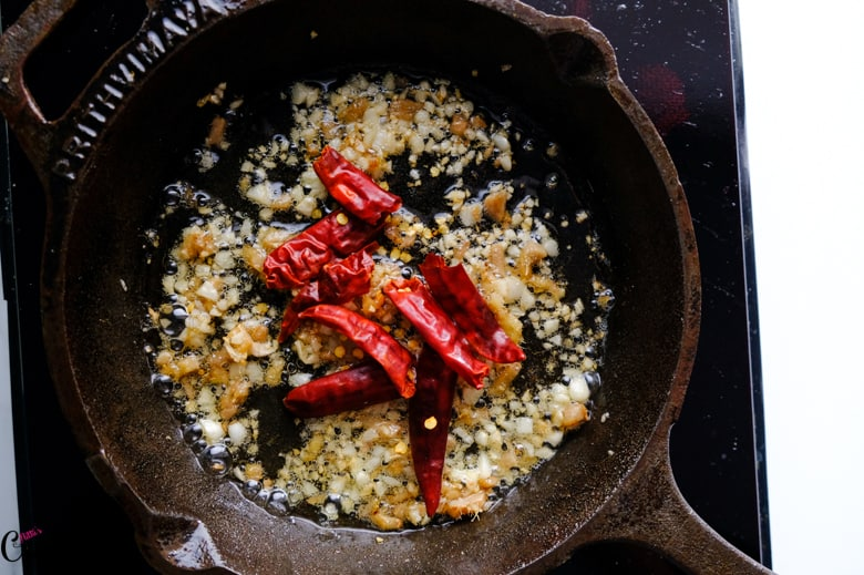 minced garlic, ginger and chillies are in iron pan
