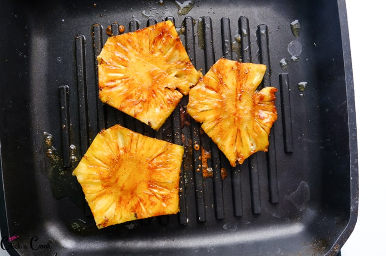 pineapple is being grilled in grill pan